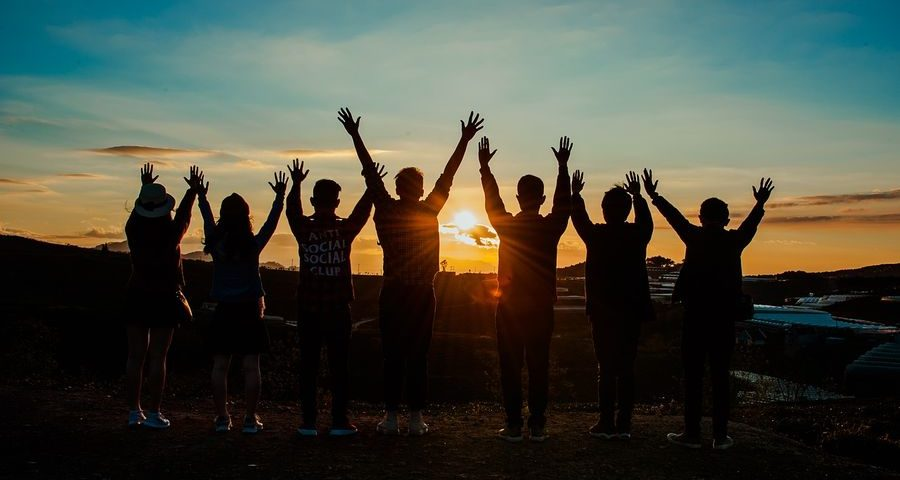 Group of teenagers arms raised in the sunset