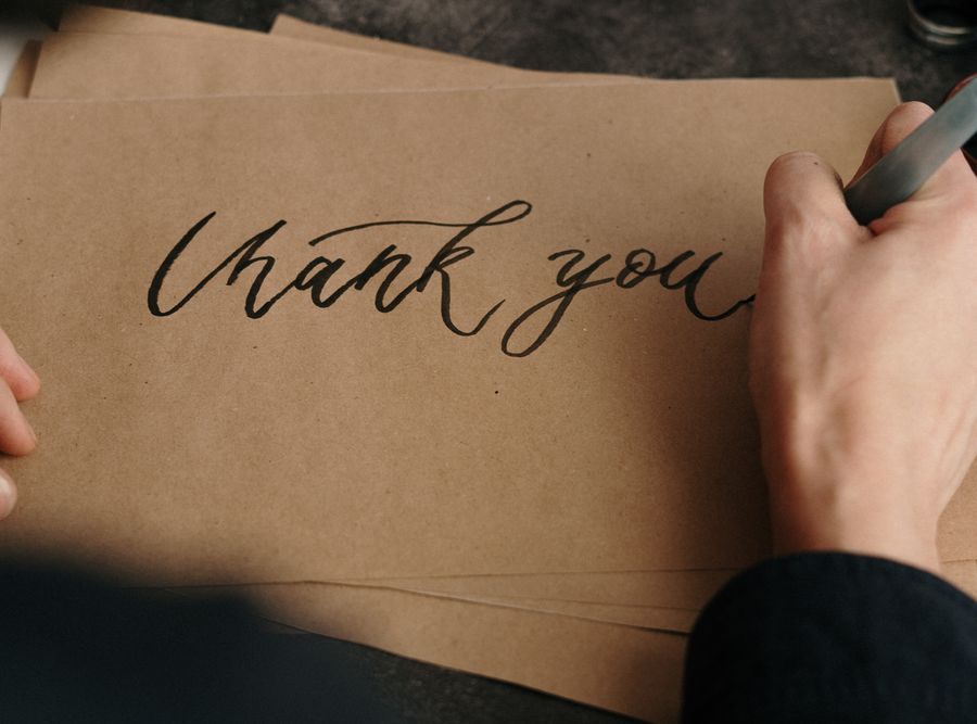 A hand writing thank you in black on a brown envelope by cottonbro from Pexels